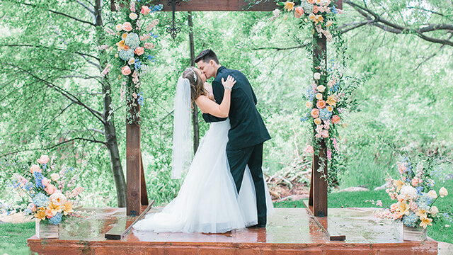 bride and groom kissing on alter with flowers